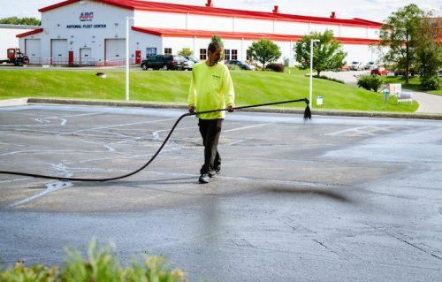 worker sealcoating asphalt